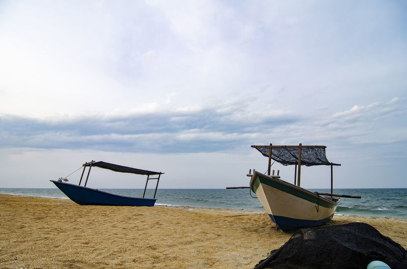 Traditional fisherman boat on the sandy beach over cloudy sky Beach Beauty In Nature Cloud - Sky Day Horizon Over Water Mode Of Transport Moored Nature Nautical Vessel No People Outdoors Sand Scenics Sea Shore Sky Tranquil Scene Tranquility Transportation Water