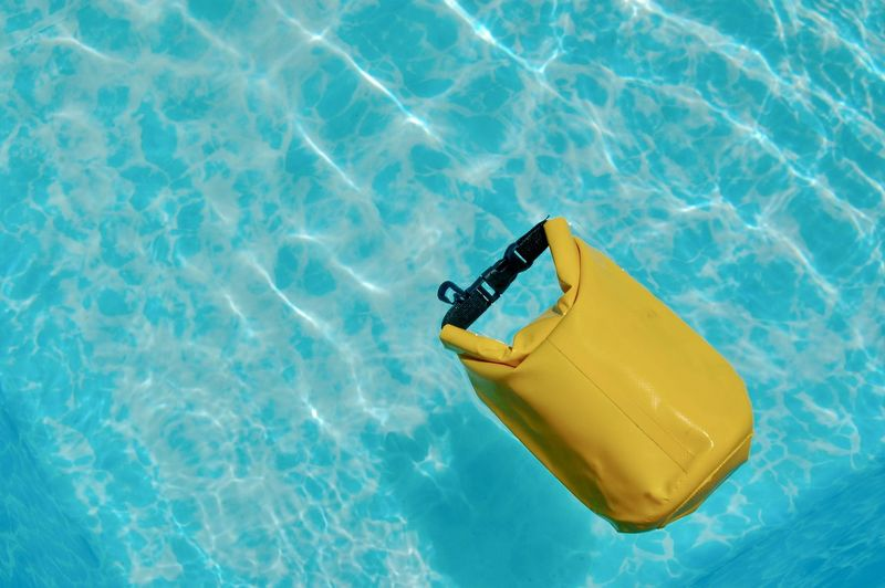 High angle view of yellow dry bag  floating on swimming pool