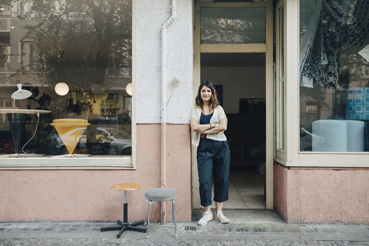 Full length of woman smiling by window