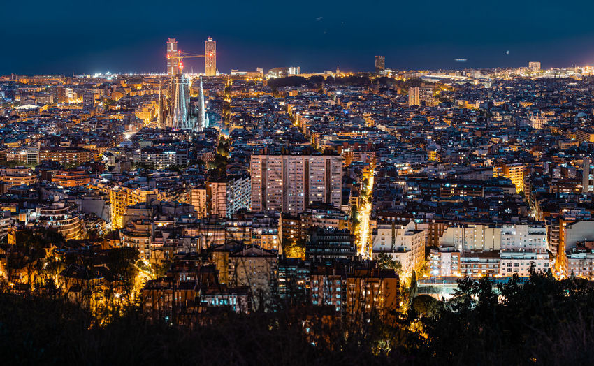 High angle view of city lit up at night. sagrada familia lit up.
