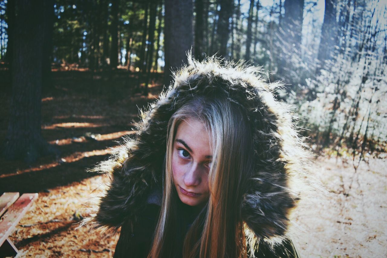 Portrait of confident girl wearing fur hood in forest