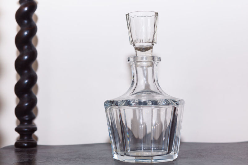 Close-up of glass on table against white background