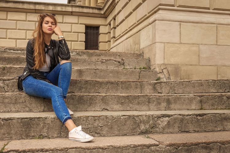 Full length of woman sitting on staircase