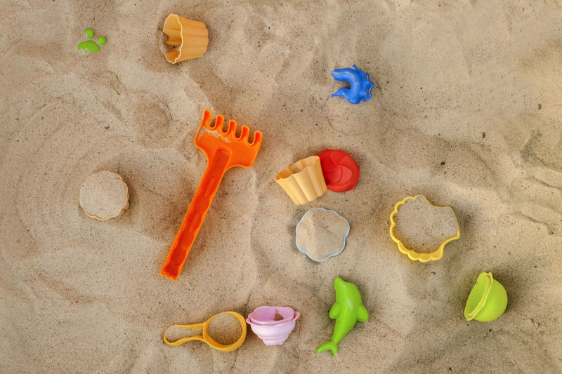 High angle view of various toys on sand