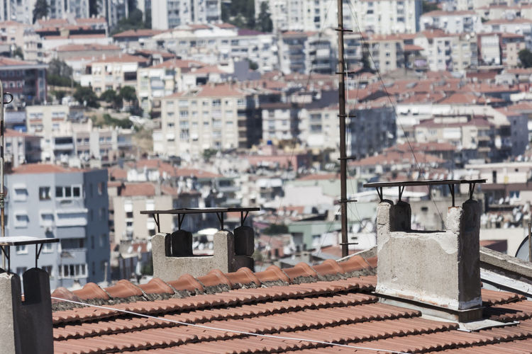 A roof with two chimneys and the city of Izmir (Turkey) in the background Chimney Construction Izmir Life Style Turkey Architecture Building Building Exterior Built Structure City Cityscape Heating System House No People Photo Population Rental Residential District Roof Roof Tile TOWNSCAPE
