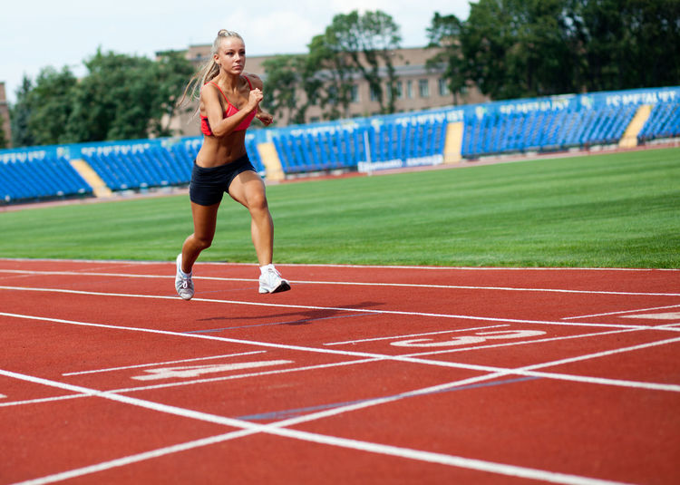 Beautiful young athletic woman in a sports suit running to the finish line Effort Running Front View Adult Determination Full Length Sports Clothing Healthy Lifestyle Women Young Adult Athlete Exercising Lifestyles Sports Track One Person Competition Running Track Track And Field Sport Real People Day