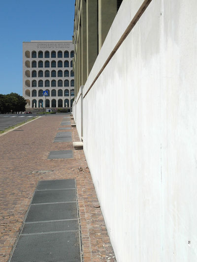 Footpath by building against clear sky