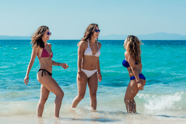 Female Friends In Bikini Smiling On Shore