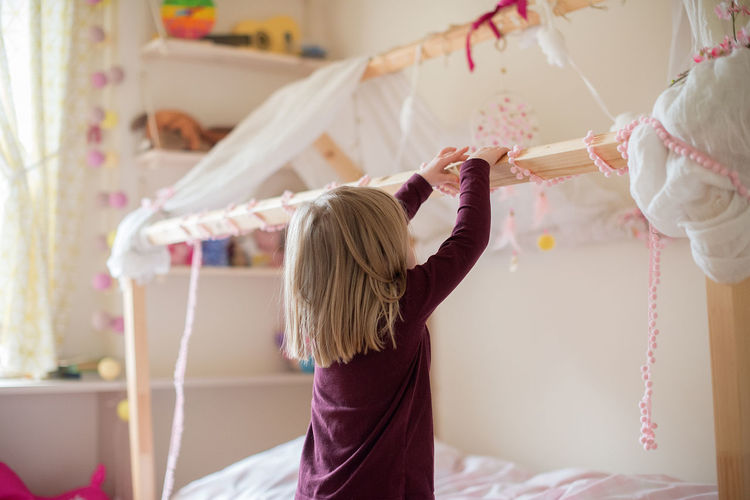 Bed Princess Room Bed Bedroom Blond Hair Child Childhood Decorated Females Focus On Foreground Girl Girls Hair Hairstyle Holding Home Interior Indoors  Innocence Kid Lifestyles One Person Preparation  Real People Rear View
