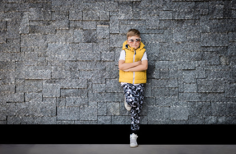Portrait of a girl standing against brick wall