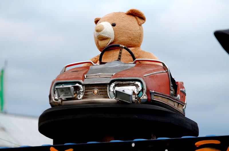 Close-up of teddy in bumper car against sky