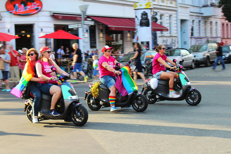 People riding motor scooter on road