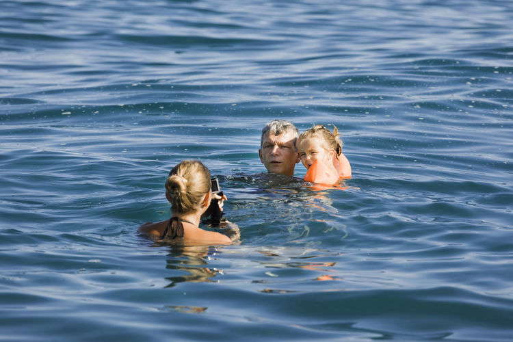 High angle view of family swimming in sea