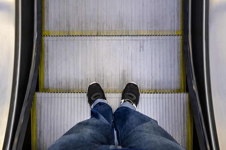 Male feet in jeans and black sneakers standing on escalator pov
