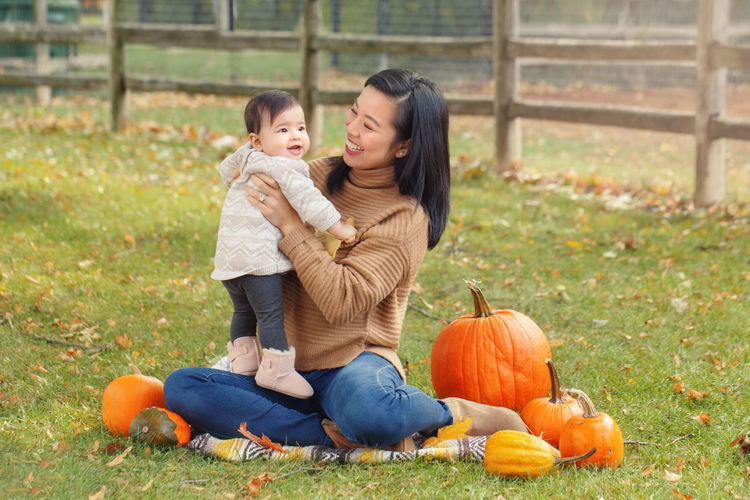 Mother carrying cute daughter while sitting on grassy land