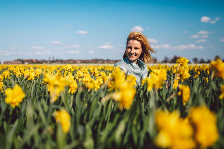 Portrait of smiling woman on narcissus field against sky