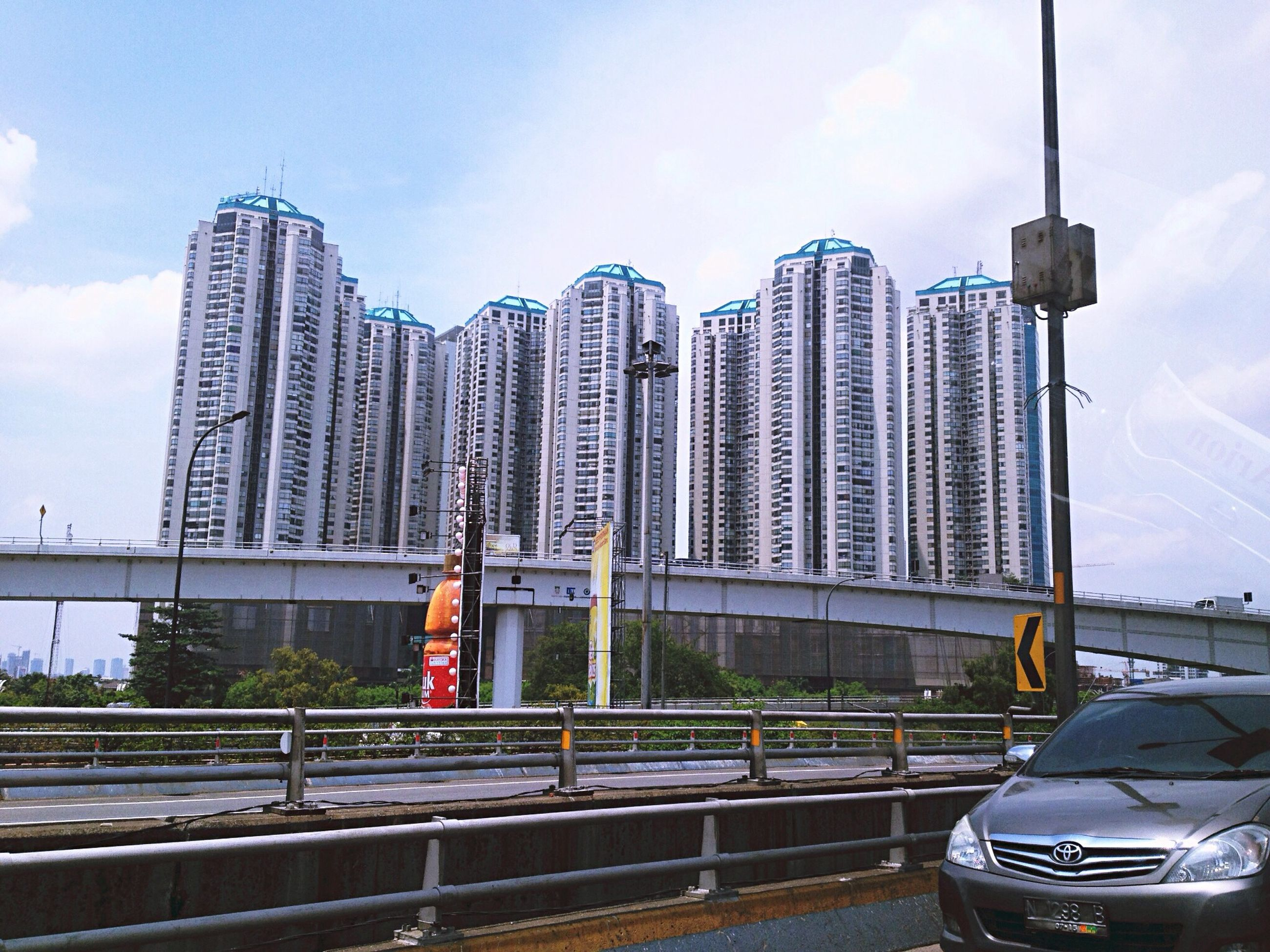 architecture, built structure, city, building exterior, sky, transportation, skyscraper, modern, street light, office building, car, mode of transport, tower, road, land vehicle, cloud - sky, city life, tall - high, railing, bridge - man made structure