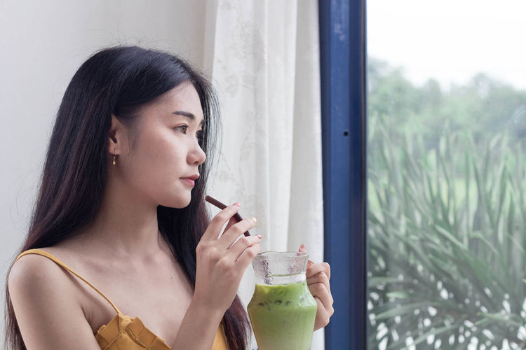 Portrait of a young woman drinking from glass window