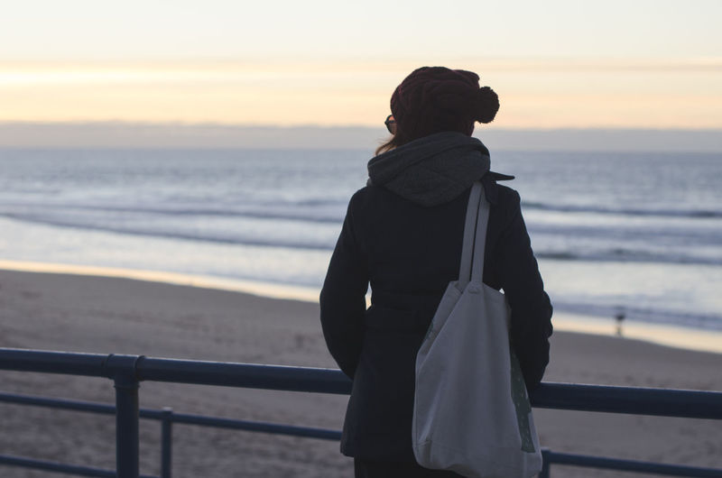 Rear view of woman standing by railing while looking at beach during sunset
