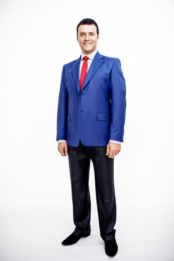 Man in classic suit on the white background. Studio shot. Business Business Stories Suit Adult Business Business Finance And Industry Business Person Businessman Clothing Formalwear Front View Full Length Happiness Indoors  Looking At Camera Males  Men Menswear One Person Portrait Smiling Standing Studio Shot Well-dressed White Background