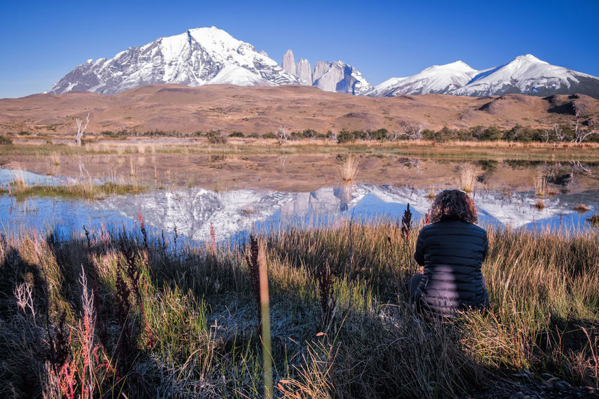 Chile Beauty In Nature Cold Temperature Day Grass Lake Mountain Mountain Peak Mountain Range Nature Non-urban Scene One Person Outdoors Patagonia Plant Real People Rear View Scenics - Nature Sky Snowcapped Mountain Torres Del Paine Tranquil Scene Tranquility Water Winter
