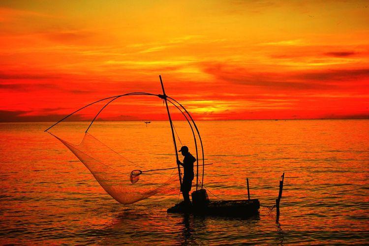 Silhouette man standing on boat in sea against orange sky