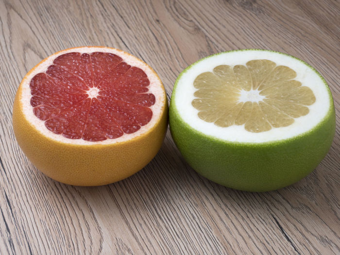 Halves of Green Sweetie and Red Grapefruit on wooden background. Close up view. Citrus, Sweet, Orange, Closeup, Fruit, Red, Food, Ripe, Green, Organic, Tropical, Vegetarian, Fresh, Juicy, Natural, Grapefruit, Vitamin, Lemon, Slice, Background, Diet, Bright, Exotic, Healthy, Ingredient, Cut, Summer, Piece, Health, Raw, Section, Delici Fruit Food And Drink Food Freshness Healthy Eating Wellbeing Cross Section No People Close-up Indoors  SLICE Wood - Material Green Color Two Objects Halved Grapefruit Table Citrus Fruit Still Life Sweet Food