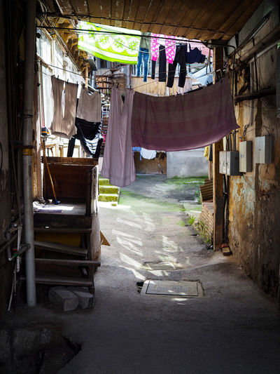 Clothes drying on alley amidst buildings