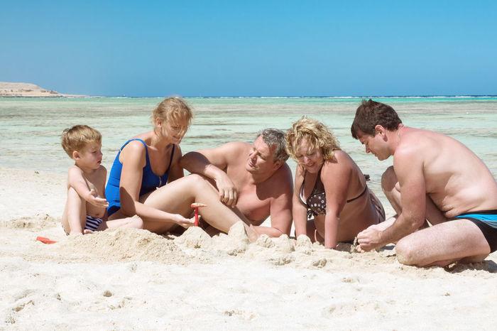 Beach Boy Build Caucasian Child Family Father Game Grandparents Horizontal Kid Man Mother Parents Rest Sand Sand Castle Son Swimming Suit  Woman