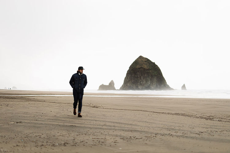 Full length of man standing on rock at beach against clear sky