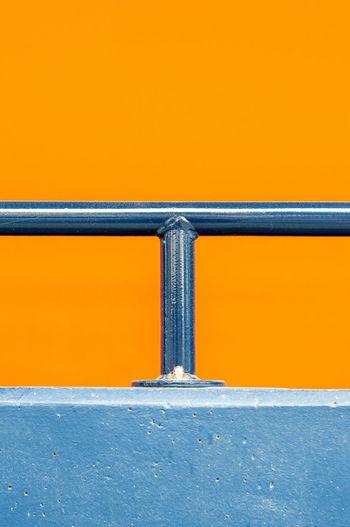 Close-Up Of Metal Railing Against Orange Background