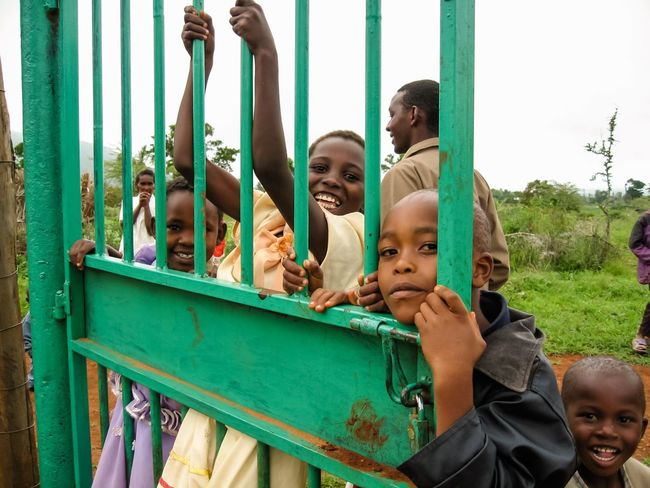 Kids Kids Being Kids Kid Children Curious Curious Kids Take My Picture Kenya Kenyan Kenyan Children Africa African African Children African Children Smiling Shy Gate Green Gate Swing From Gate Sunday Best Sunday Dress
