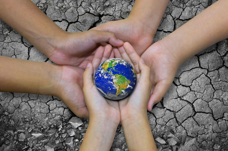 Cropped hands holding planet earth