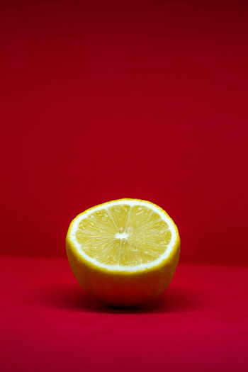 Close-up of lemon slice against red background