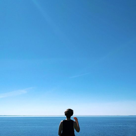 Rear view of man standing at beach against clear blue sky