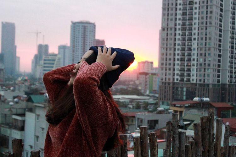 Side View Of Teenage Girl With Head In Hands Standing Against Buildings During Sunset