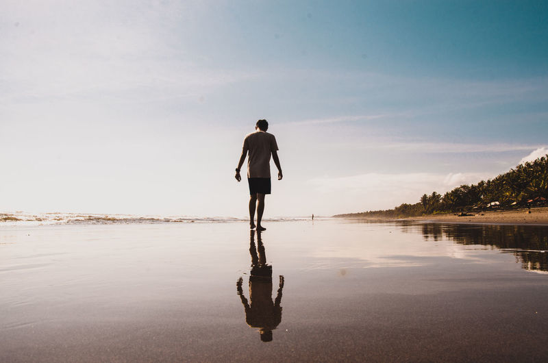 Rear view of man walking at beach against sky