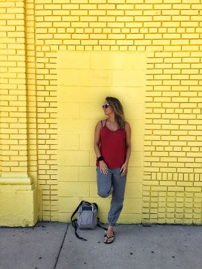 Full length of woman leaning on yellow brick wall