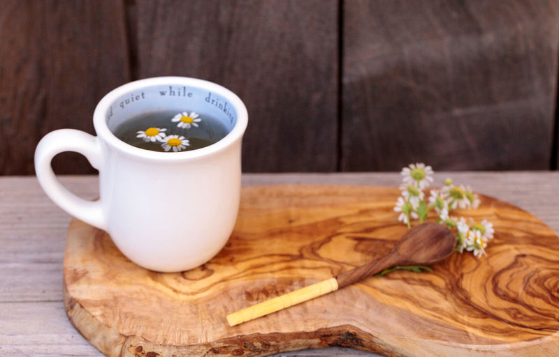 Chamomile tea with daisies in cup on cutting board over table