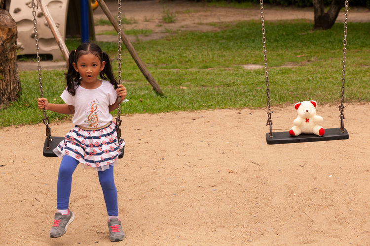 Full length of a smiling girl on swing at playground