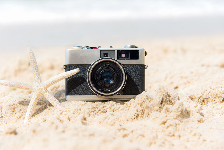 Close-up of camera on sand at beach