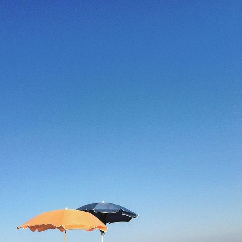 Orange And Blue Parasols Against Clear Sky