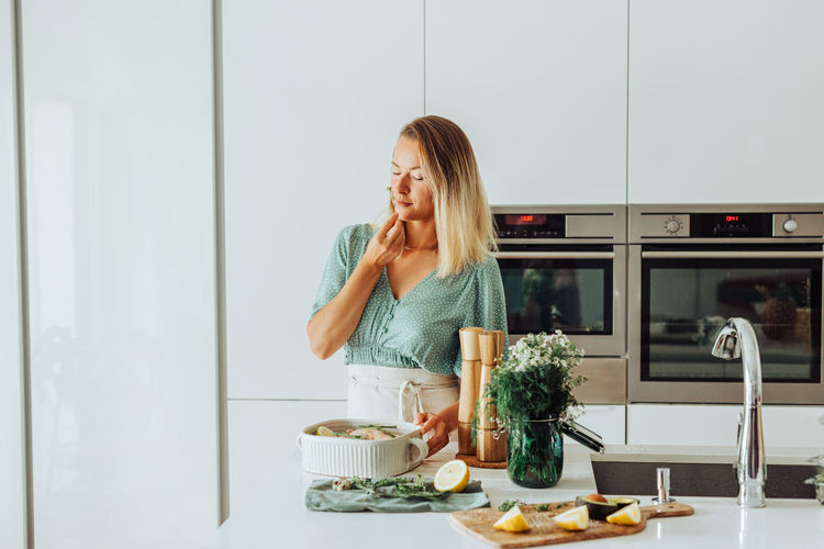 Woman eating food in kitchen at home