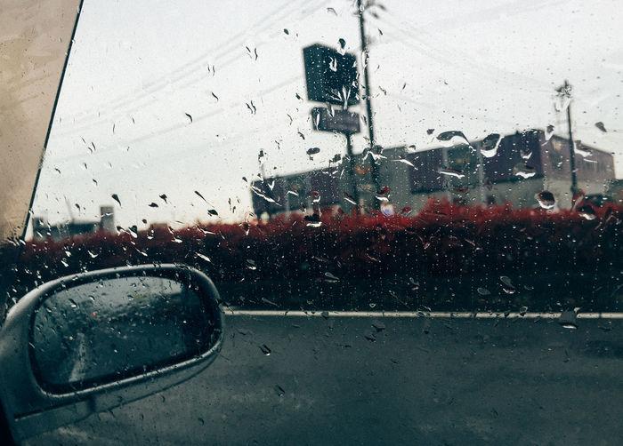 Road seen through wet car windshield
