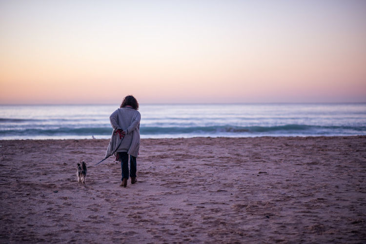 Rear view of woman with dog at beach during sunset