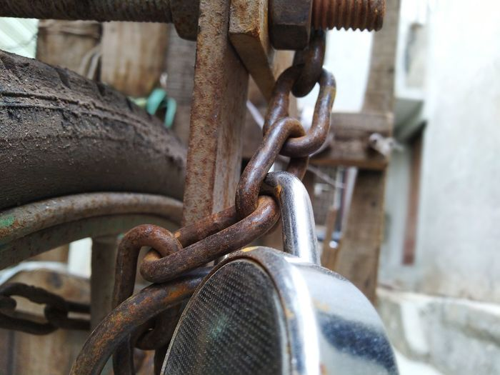 Close-up of lock hanging on rusty chain