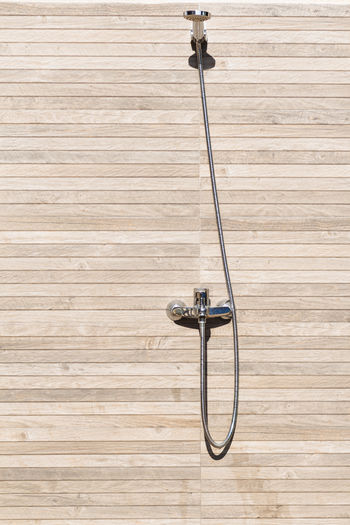 Low angle view of electric lamp against wooden wall