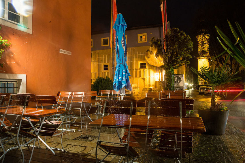 A restaurant's terrace stands empty during heavy rainfalls Architecture Bavaria Building Exterior Built Structure Burghausen Chair City Germany Illuminated Night No People Outdoors Rain Restaurant Spring Terrace Tree