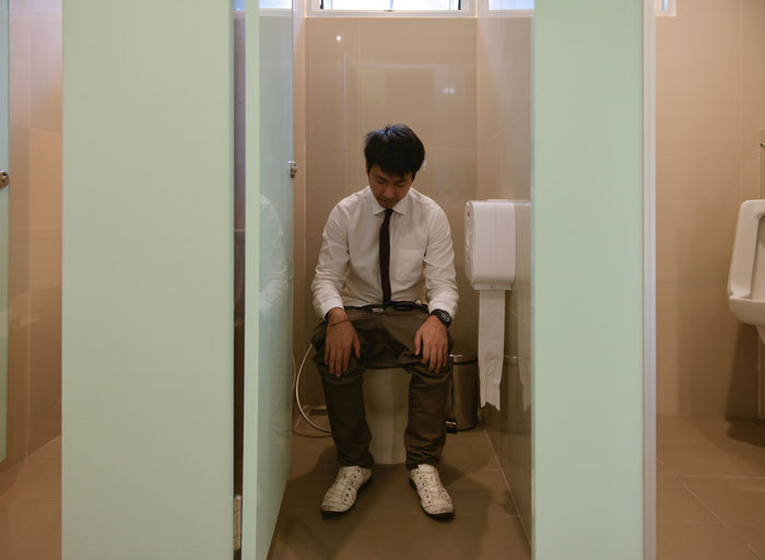 An Asian business man pooping in bathroom, diarrhea Corridor Day Front View Full Length Indoors  Men One Person People Pooping Real People Sitting Standing Young Adult