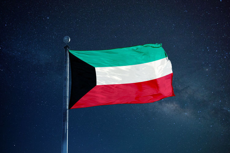 Low angle view of kuwaiti flag against star field sky